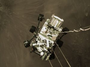 "The earliest pictures sent back were made during the rover's descent. Here, Perseverance is being lowered on three nylon ropes and an ""umbilical cord"". When the rover's wheels touched the ground, the tethers were severed."