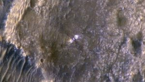Perseverance can be seen in this enhanced colour image at its landing site, six days after touchdown. You can see the two bright zones to the sides of the rover that have been scoured clear by the descent stage rockets and the dark material appears to have been funnelled outward both in front and behind the rover.